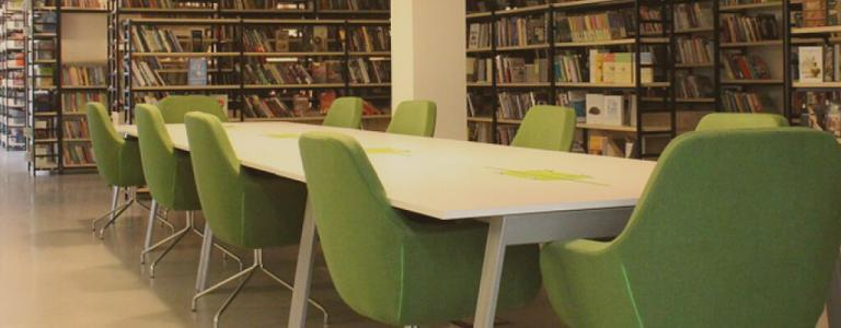 A table with green chairs inside a library